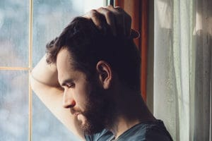 man considering addiction treatment programs while looking out window